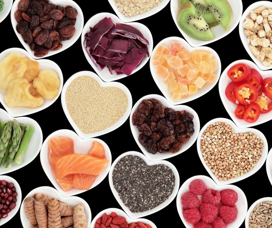 heart shaped bowls of healthy food such as fruits, vegetables, protiens, and whole grains.