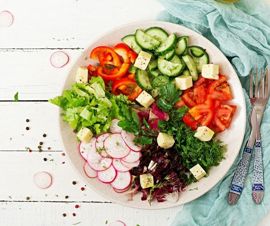 bowl of cut up vegetables arranged in groups on a table with a few sprinkled to the side and a blue napkin