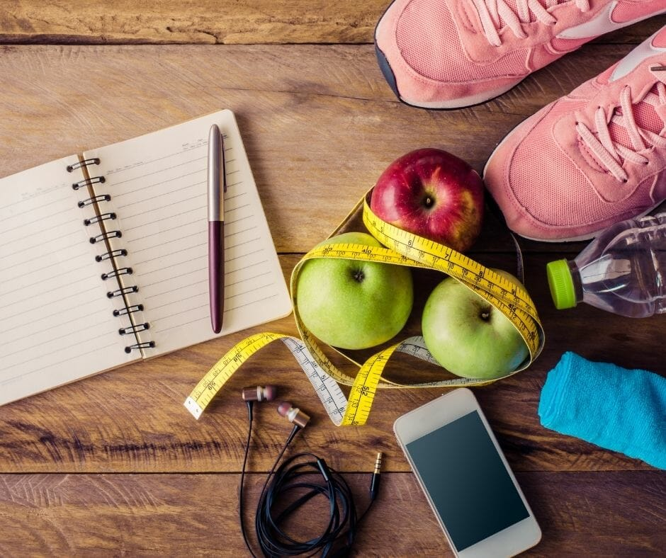 fitness journal, fruit, shoes, and tools for fitness journey