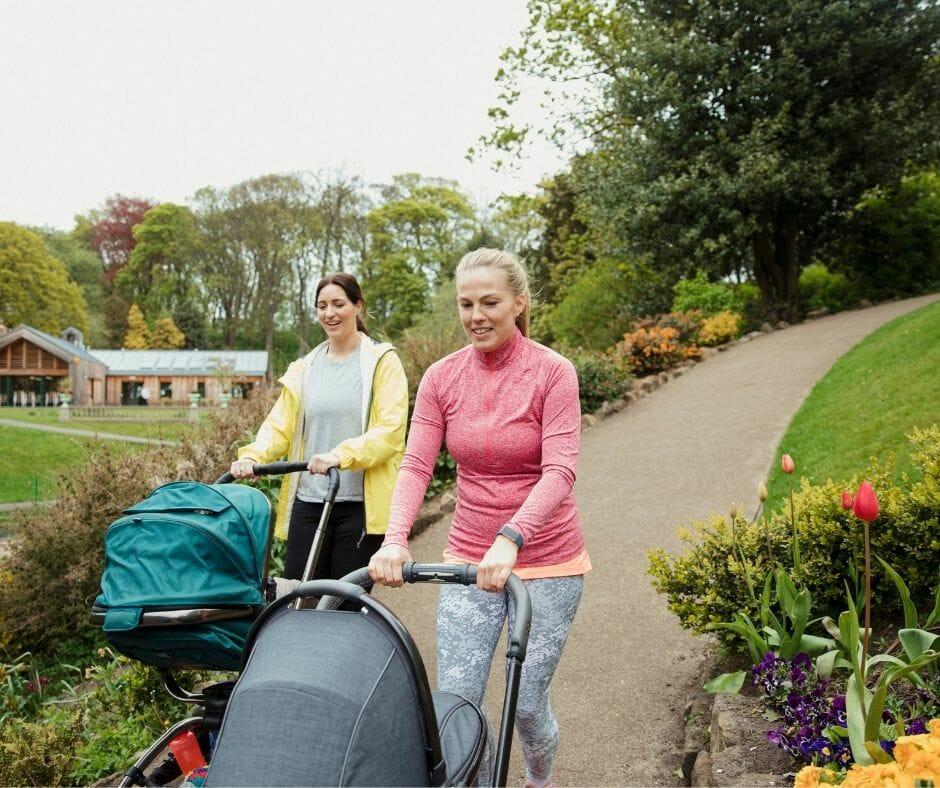 two women walking pushing baby strollers