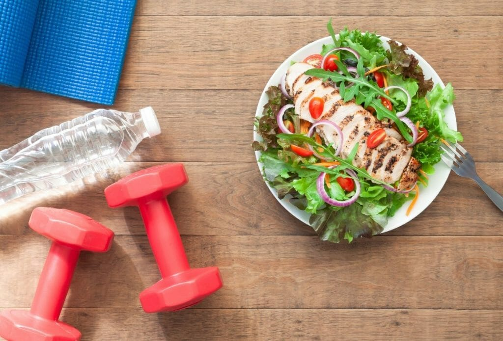 table with healthy plate, smart bells, water bottle and exercise mat to show the importance of habits that are good