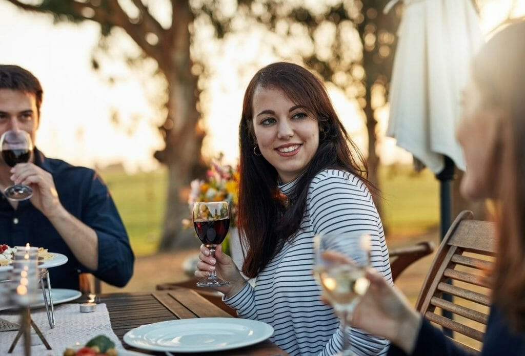 friends sharing dinner and wine at a table outside