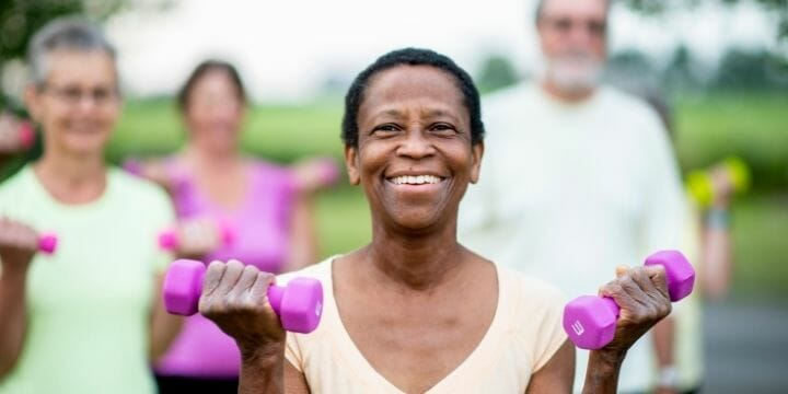 woman with dumbbells smiling