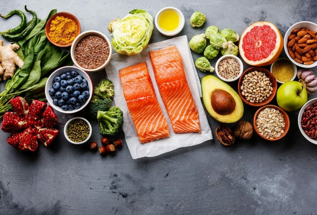 healthy food laid out on a board including salmon, avocado, blueberries and other bowls of fruits and vegetables and whole grains