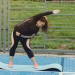 overweight woman doing side bends on exercise mat outside