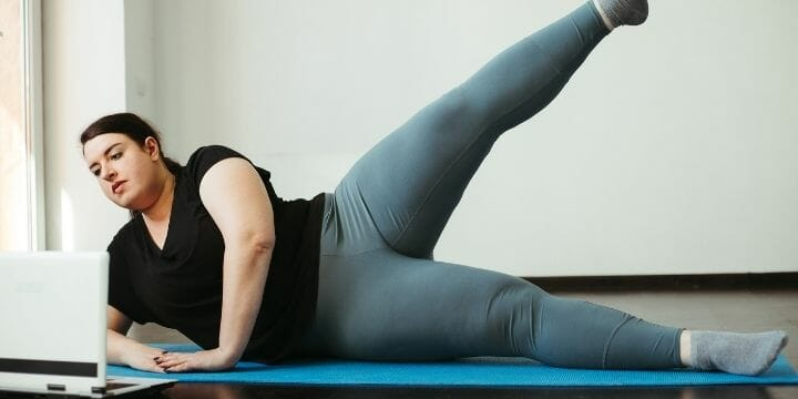 woman doing leg lift on exercise mat, beginner