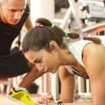 woman planking while personal trainer times her