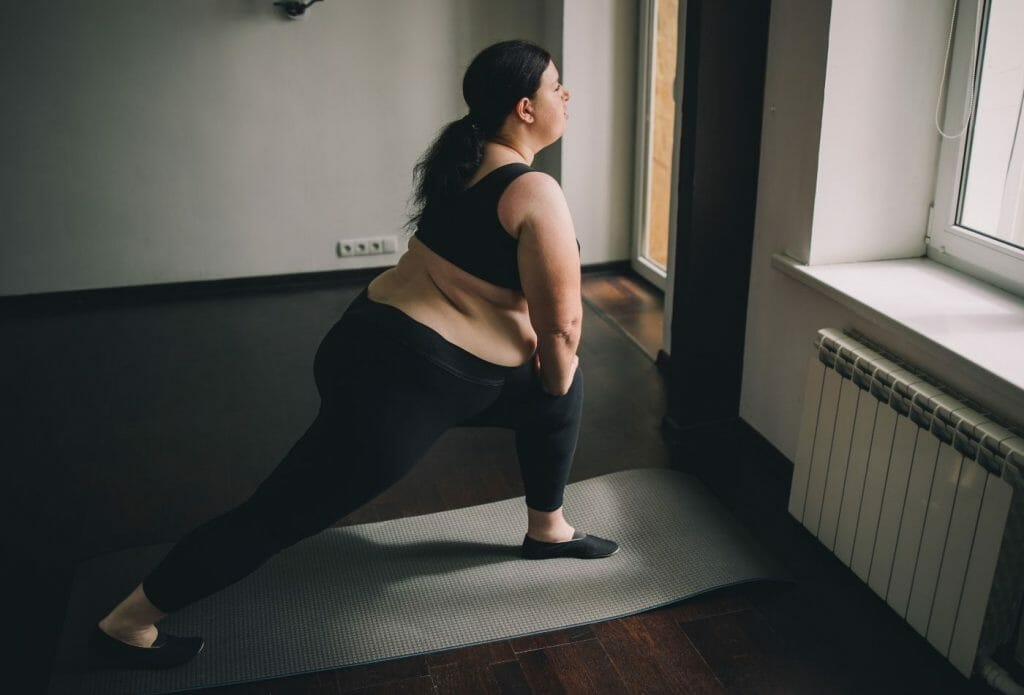 obese woman stretching at home