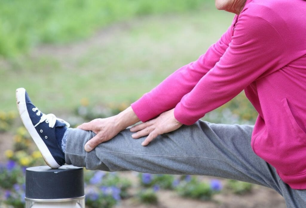 woman leaning against post doing hamstring stretch