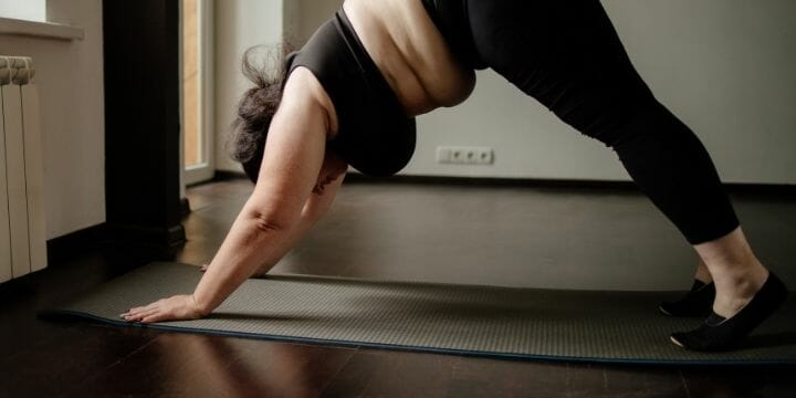 obese beginner at home doing yoga on a mat