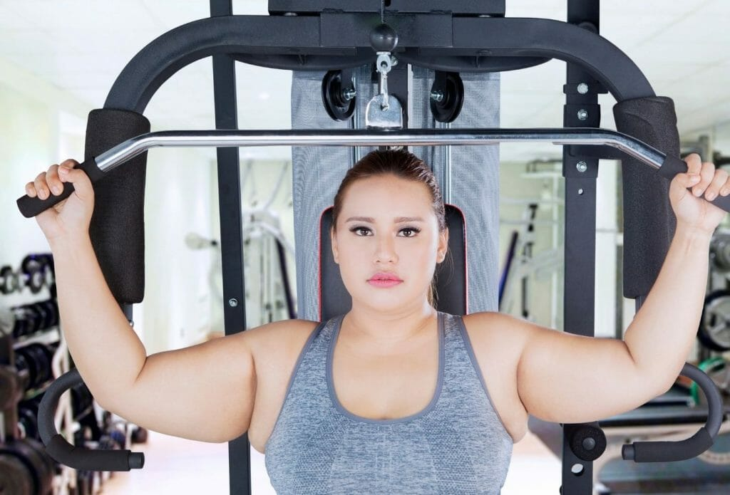 obese beginner using machine for shoulder press to do strength training