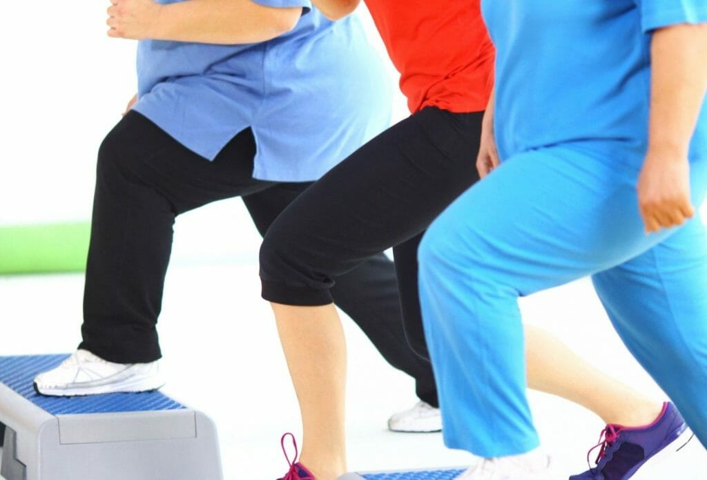 overweight women using a step for exercise
