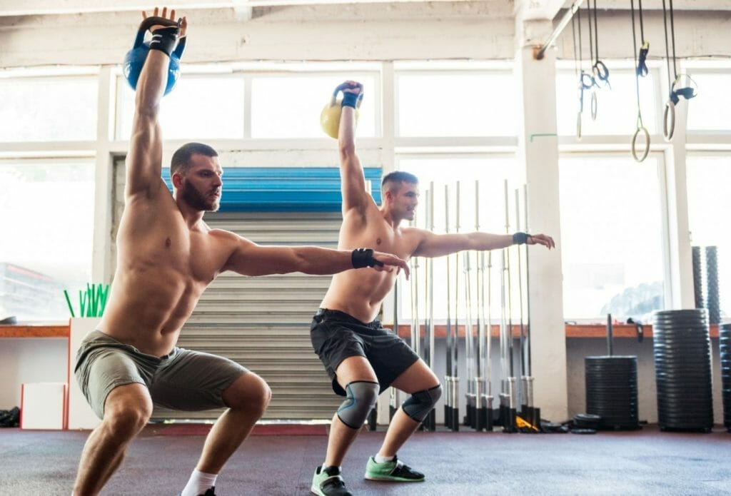 men working out with weights to achieve their smart fitness goals.