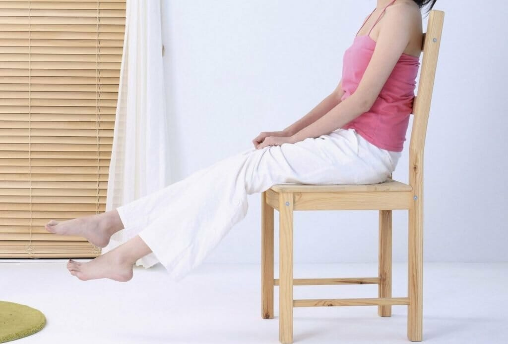 woman sitting on a chair doing seated leg lifts