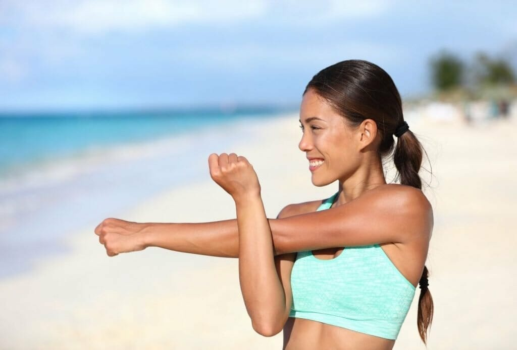 woman on the beach doing shoulder stretch