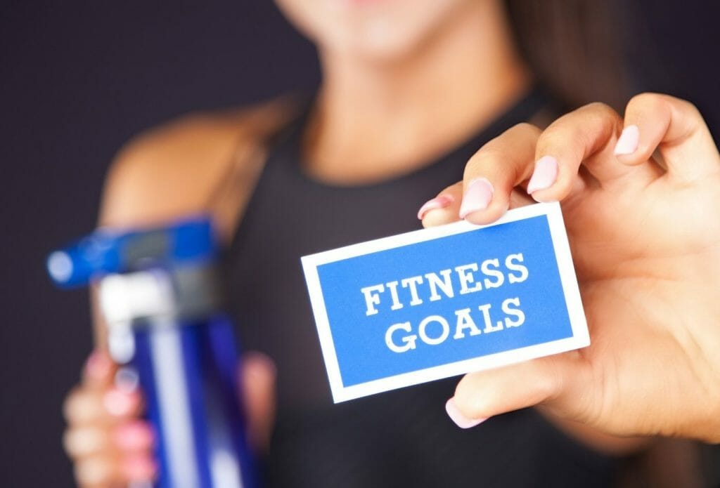 woman holding a water bottle and a card that says fitness goals