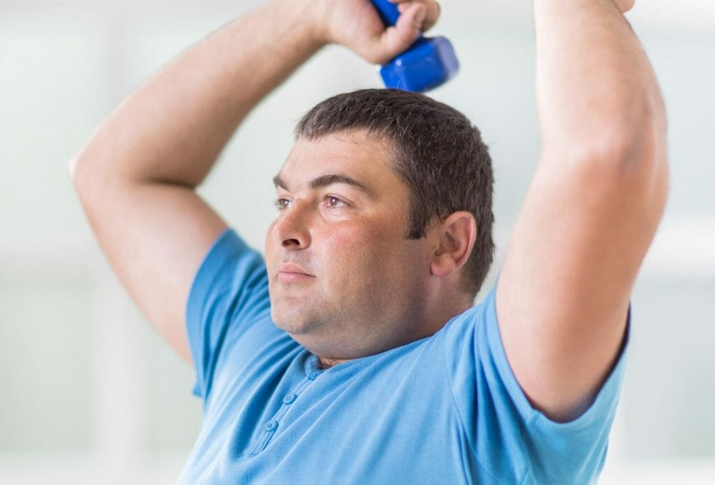 overweight man using dumbells for strength training