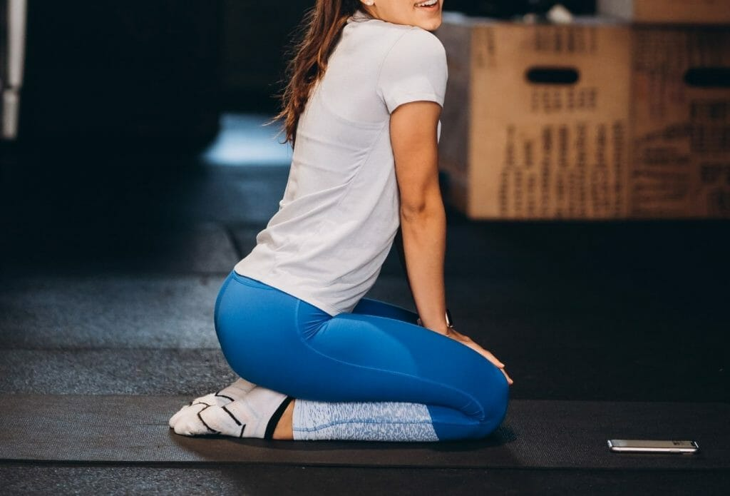 woman doing stretches for shin splints sitting on her feet