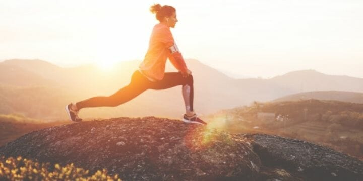 woman stretching on a mountain with the sun shining behind her