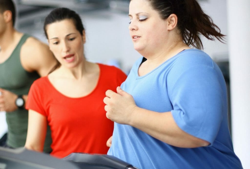 obese woman working out on treadmill with personal trainer