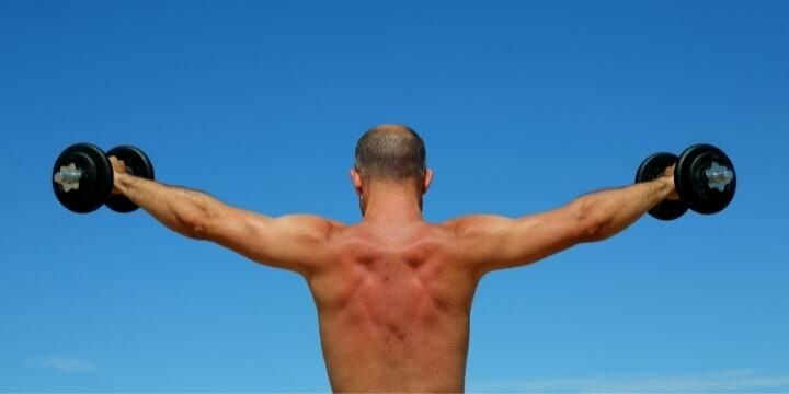 man standing with weights in his hands, lifting them up evenly on each side, balanced