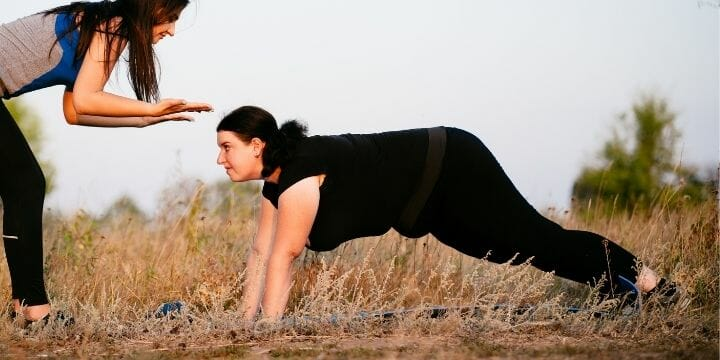 obese woman doing push up outside with a trainer