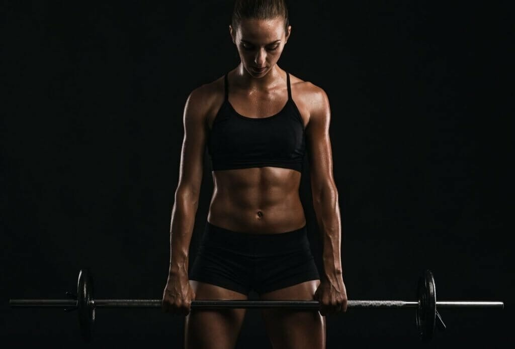 a strong woman lifting a barbell with balanced weights